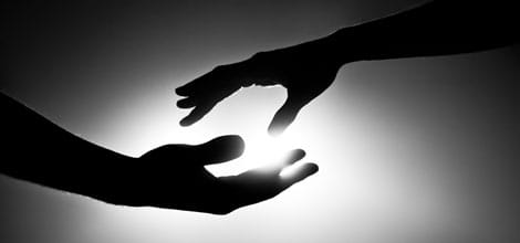 Silhouette of two hands reaching for each other