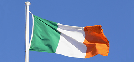 Image of Irish flag blowing in the wind on a blue sky