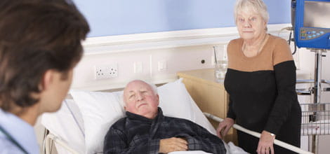Senior couple talking to doctor in hospital